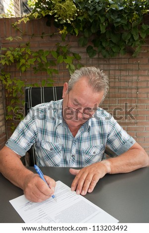 Handsome Senior signing a legal contract  in his backyard - stock photo