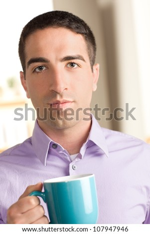 Handsome serious guy looking at the camera holding a blue coffee mug wearing a purple shirt
