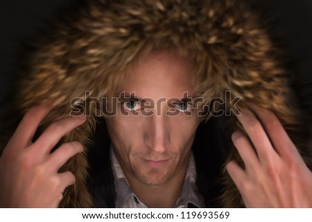 Handsome serious man in winter clothing peering up at the camera from underneath the warmth of his fur trimmed hood. Portrait of angry guy