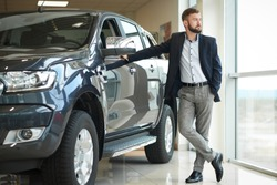 Handsome serious man standing and posing near dark blue jeep and big window in car center. Businessman wearing in dark blue jacket and blue shirt. Customer purchasing new auto.