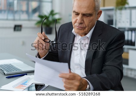 Handsome serious mature businessman in dark blazer and white shirt checking forms while holding eyeglasses #518289268
