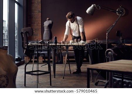 Shutterstock Handsome serious tailor in white shirt with brown leather suspenders working near wooden table with threads, apron and scissors in amazing atelier with antique furniture and mannequin on background