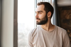 Handsome serious young bearded man standing at the window at home, looking away