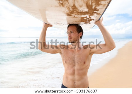 Handsome sexy active sporty topless man carrying his surfboard on the head. Surfer lifestyle on Hawaii beach during summer travel vacation. Caucasian athlete going out surfing with surf board. #503196607