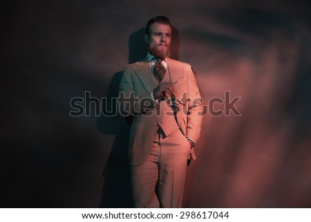 Handsome sexy bearded man in a stylish suit standing leaning against a wall in red toned atmospheric lighting, with copyspace