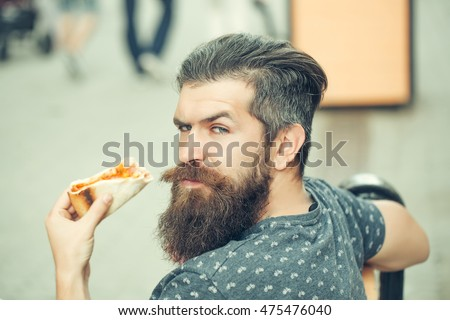 handsome sexy bearded young man hipster with long beard and mustache on serious hairy face eating pizza sitting on street bench outdoor