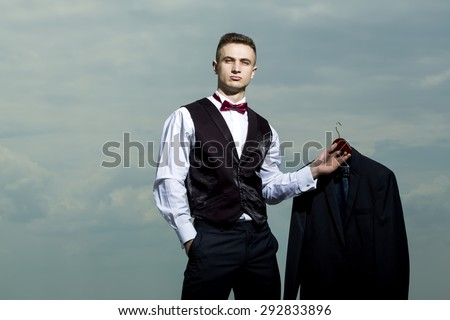 Handsome sexy brutal strong muscular man in formal suit with bow tie holding jacket standing on blue sky background copyspace, horizontal picture