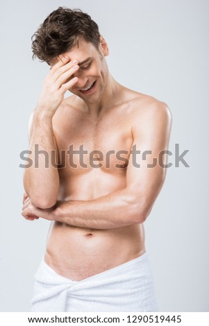 handsome sexy laughing man posing in towel isolated on grey