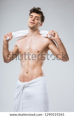 handsome sexy man posing with white towel isolated on grey