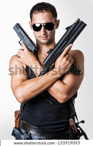 Handsome sexy  military man wearing black fashion sunglasses with automatic and hand gun