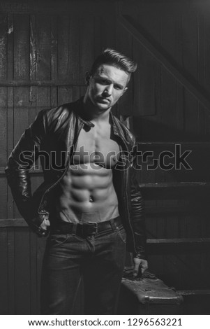 Handsome sexy sensual muscular stylish young man in leather jacket with bare torso standing with retro suit case near stairs indoor on wooden background, vertical picture