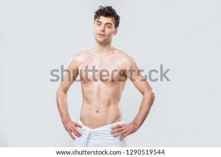 handsome sexy shirtless man posing in towel isolated on grey