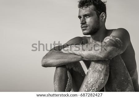 Handsome sexy topless male model relaxed sitting on the beach. Black and White. #687282427