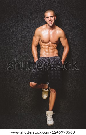 Handsome shirtless fitness man in gray shorts, smiling and posing against dark gray background. Mild retouch, studio lighting.