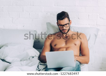 handsome shirtless male freelancer with muscular torso working on laptop in bed at home