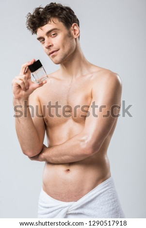 handsome shirtless man holding bottle of perfumes, isolated on grey