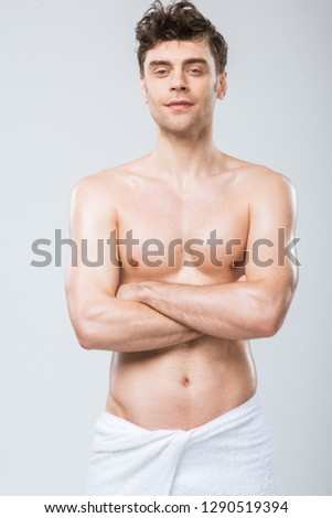 handsome shirtless man in towel posing with crossed arms isolated on grey