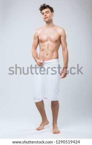 handsome shirtless man posing in towel isolated on grey