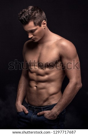 Handsome shirtless man posing on black studio background.
