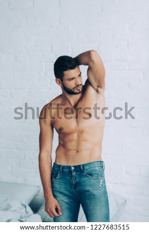 handsome shirtless man with muscular torso posing in bedroom at home