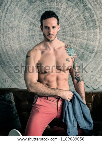 Handsome shirtless muscular man at home laying on couch