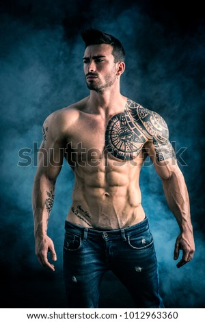 Handsome shirtless muscular man with jeans, standing, on dark smoky background in studio shot. Tattoo reads: We are free to start again, in Italian
