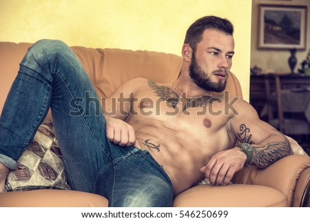 Handsome shirtless muscular young man at home laying on couch #546250699