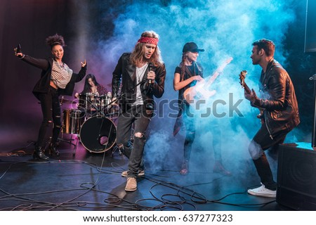 Handsome singer with rock and roll band performing music on stage #637277323