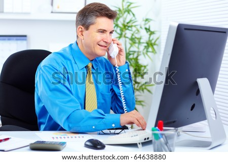 Handsome smiling businessman calling by phone in the office