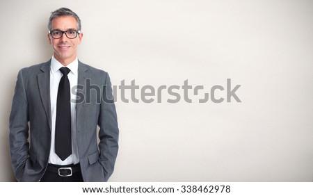 Handsome smiling businessman over gray banner background.