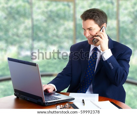 Handsome smiling businessman working with laptop.