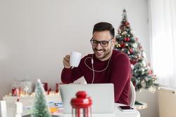 Handsome smiling freelancer enjoying at home for Christmas