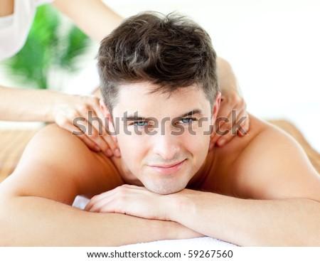 Handsome smiling man enjoying a back massage in a spa center