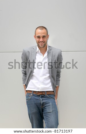 Handsome smiling man leaning on wall