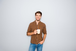 Handsome smiling man with cup of coffee isolated on gray background