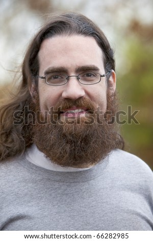 Handsome smiling man with long hair, beard and glasses outdoors in Autumn season