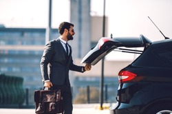 Handsome smiling positive Caucasian bearded businessman in suit with sunglasses holding his briefcase and closing trunk on his car.