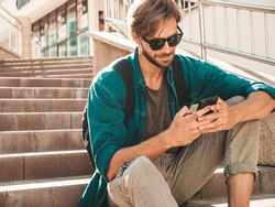 Handsome smiling stylish hipster lambersexual model.Man dressed in white T-shirt.Fashion male sitting on the stairs. Holding, scrolling and texting in his cellphone. Writes sms on smartphone