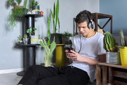 Handsome smiling teenager boy in headphones with smartphone sitting at home, listening music audio blog book, resting, playing, studies. Education leisure lifestyle teens concept