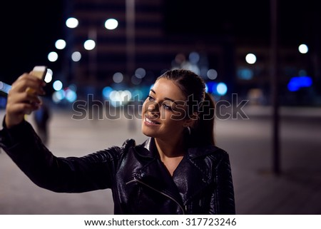 Handsome smiling women taking a selfie with her mobile phone. Selective focus.
