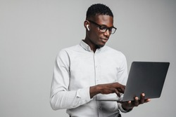 Handsome smiling young african business man in wireless earphones using laptop computer isolated over gray background, wearing white formal shirt