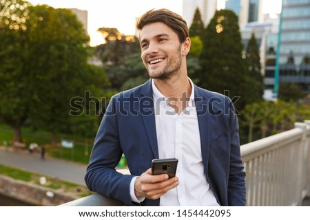 Handsome smiling young businessman smartly dressed leaning on a rail while standing outdoors at the city street, holding mobile phone