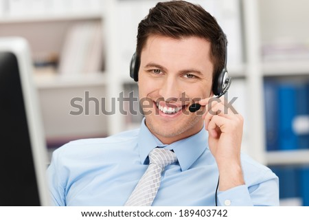 Handsome smiling young businessman using a headset conceptual of a call centre, client services, telemarketing or hands free office communication