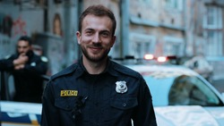 Handsome smiling young man cops stand near patrol car look at camera enforcement officer police uniform auto safety security communication control policeman close up slow motion