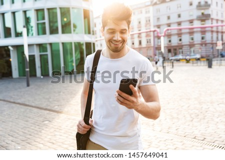 Handsome smiling young man dressed casually spending time outdoors at the city, holding mobile phone