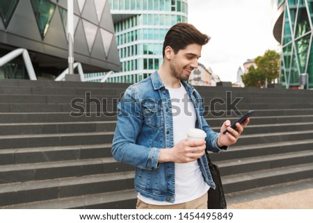 Handsome smiling young man dressed casually spending time outdoors at the city, holding takeaway coffee cup while texting