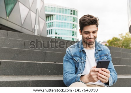 Handsome smiling young man dressed casually spending time outdoors at the city, sitting on stairs