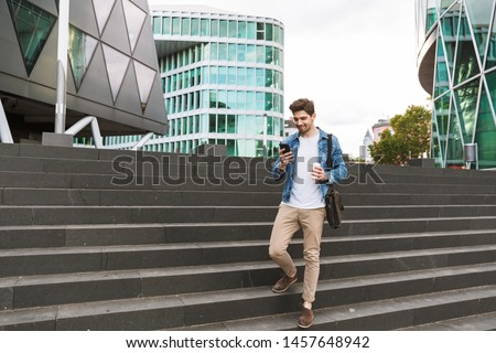 Handsome smiling young man dressed casually spending time outdoors at the city, using mobile phone while walking down stairs