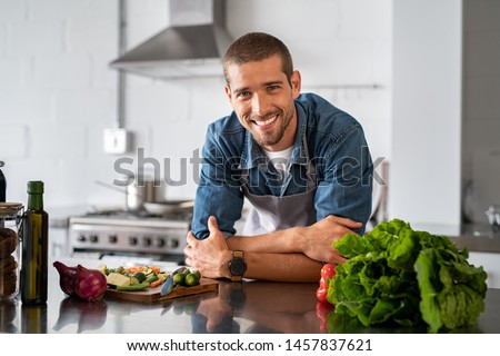Handsome smiling young man leaning on kitchen counter with vegetables and looking at camera. Portrait of happy casual guy in apron leaning on steel counter in the kitchen with ingredients on it.