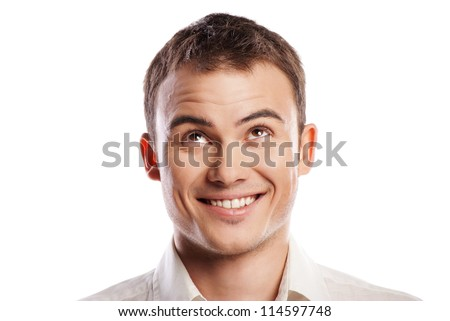 Handsome smiling young man looking up over white background